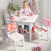 Little girl sitting at white, children's table painted with numbers; chairs with patterned, fabric backrest covers