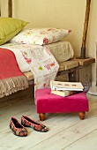 Footstool with pink cover next to bed made from mattress on rustic wooden boards