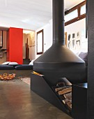 Black, suspended fireplace and firewood store in interior with black loungers in front of red pillar in background