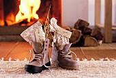 St. Nicholas gifts with name tags in laced boots in front of open fire