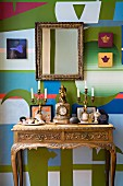Antique mantel clock flanked by candlesticks on Baroque console table and gilt-framed mirror on artistically painted wall