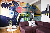 Artist in front of creative, graphic mural; aubergine corner sofa and vintage side table