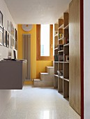 Corridor with fitted, multiplex wood shelves and steps leading to integrated loft bed along yellow-painted wall at far end