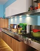 Designerküche mit integriertem Gasherd und Spüle in Edelstahlarbeitsfläche, weisse Hängeschränke und schwebende Unterschränke aus Holz