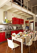 White dining area with festively set dining table and kitchen counter with red, glossy fronts in high-ceilinged interior with gallery