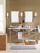 Doppelwaschbecken in grauer Marmorplatte auf Chromgestell, in warmem Taupe geflieste Rückwand und geflochtene Wäschekörbe