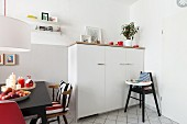A half-height white cupboard with a highchair in front of it with and eating area to the side with a black table in a renovated living-kitchen area