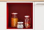 Storage jars in an open, red shelf within a kitchen cupboard