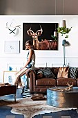 Safari-style lounge - animal skins and hunting trophies on floor, wall and coffee table and young woman perched on arm of brown leather sofa