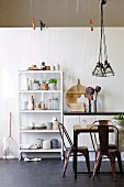 Retro-style metal chairs, dining table and shelves of bottled and storage jars against white-painted wooden wall