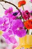 Orchideenblüte mit Anemonen und Ranunkeln in gelber Vase