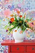 Bouquet of multicoloured tulips on red, Oriental chest of drawers against floral wallpaper