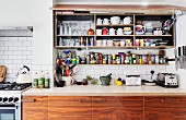 Kitchen wall cabinet with open lift-up door above spice rack and base units of recycled wood