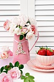 Metal jug of delicate pink roses and china bowl of strawberries