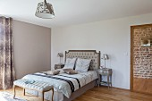 Upholstered, Rococo bench at foot of double bed with button-tufted headboard in simple bedroom