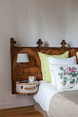 Bed with antique, carved wooden headboard; table lamp on small, retro case mounted on headboard as bedside table