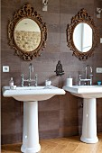 Twin pedestal sinks below mirrors with ornate, gilt frames on tiled wall