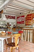 Chairs of various styles around rustic table, kitchen counter with curtains on base units and vintage advertising signs