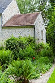 Farne im Garten vor Natursteinhaus mit Anbau