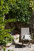 Wooden chair on sunny stone-paved terrace against façade densely covered in climbers