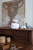 Jewellery, storage baskets and canvas with urn motif on antique bureau