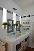 White washstand with twin sinks and mirrors between narrow windows in modern bathroom with tiled frieze