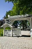 Paved drive with porch over wooden gate and pedestrian gate to one side