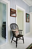 Windsor chair in hallway with pastel-blue wood panelling and white door frames