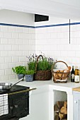 Masonry kitchen counter with integrated, antique iron cooker; potted herbs and basket of bread