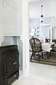 Blick von Diele mit eisernem Holzofen in Landhaus Wohnküche mit Windsor-Stühlen