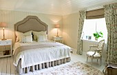 Grand double bed with curved headboard in country-house bedroom with pale wood panelling and fabrics with small floral patterns