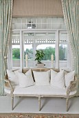 Delicate, antique bench with cane backrest in front of window element with view into conservatory