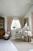 White wicker chair and side table in seating area below window in wood-panelled room