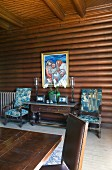 Table with drawers flanked by armchairs below painting in log-cabin-style dining room