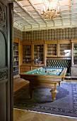 Historischer Raum für gesellige Zusammenkünfte mit Glasschrank und integrierter Lederbank, Bibliothek und zentralem Billardtisch