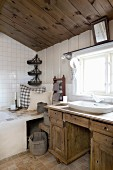 Rustic wooden washstand below window and cushions on corner of bathtub