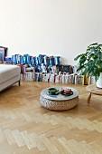 Am Boden vor der Wand aufgereihte Bücher und Sitzpouf mit Geschirrtablett als Coffeetable in grosszügigem Altbauwohnraum