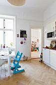Esstisch und blauer Kinderstuhl in weisser Wohnküche; Blick in das Kinderzimmer im Hintergrund