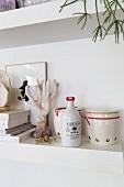 Ceramic oil bottle and retro storage jars on white shelf