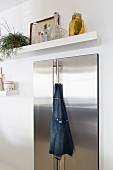 Cooks' apron hanging from handle of stainless steel fridge below white floating shelf