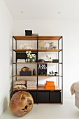 Wooden ball on floor in front of shelves with black metal frame and wooden shelves in corner of bedroom
