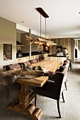 Rustic, solid-wood table and brown upholstered chairs in open-plan interior in various shades of brown