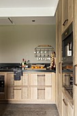 Fitted kitchen with solid-wood doors and taupe wall