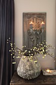 Vintage vase of flowering branches on table below lit candles on carved wooden candle scone