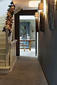 Hallway with festively decorated balustrade and view of dining area through open door
