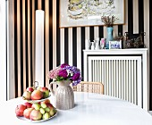 Fruit on cake stand and vase of flowers on white table in front of cylindrical standard lamp against black and white striped wallpaper