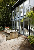 Contemporary house with glass and steel façade and weathered wooden table and bench on tiled terrace