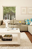 White coffee table on castors and ecru sofa in modern interior