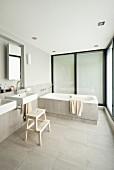 Minimalist designer bathroom with sinks below mirror in niche and bathtub