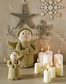 Christmas arrangement: candles, knitted angels and stars and snowflakes on wall